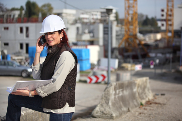 Project manager kneeling, with a binder and cell phone, at a jobsite.