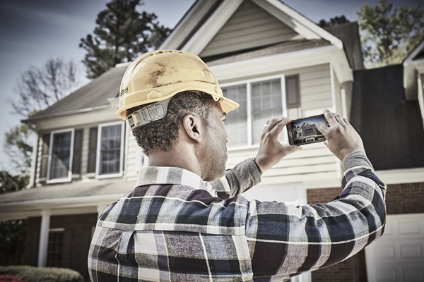 Contractor talking photos of a house for 3D measurements