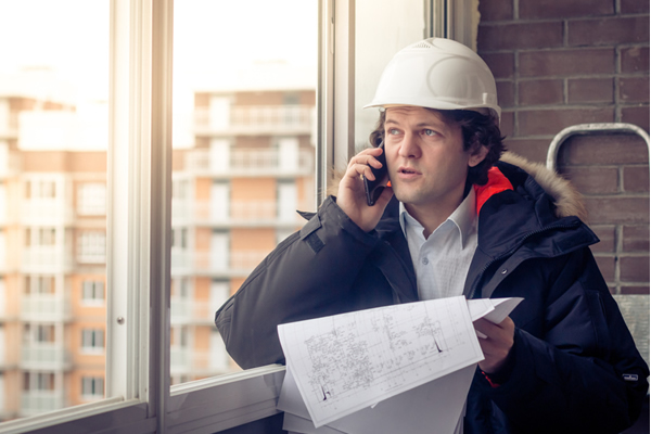 contractor in winter coat speaks on a phone standing next to a window