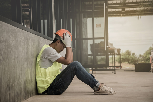 Worried contractor sitting in front of a cement wall