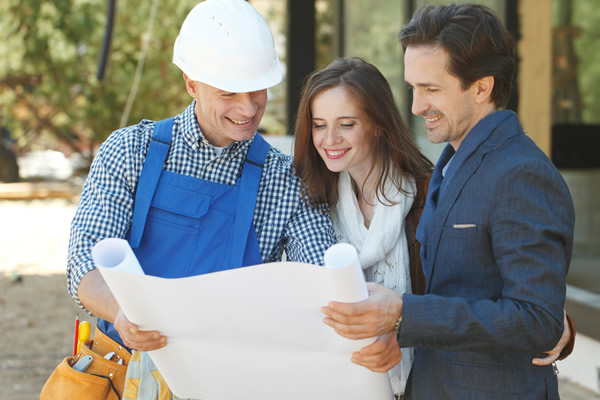 Contractor and homeowners looking at blueprint outdoors