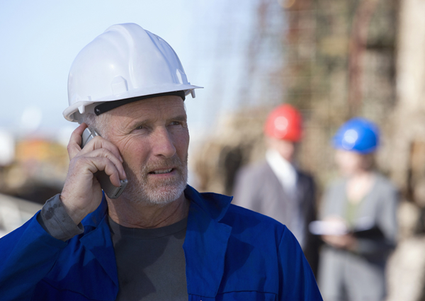 Worried contractor talking on a cell phone.
