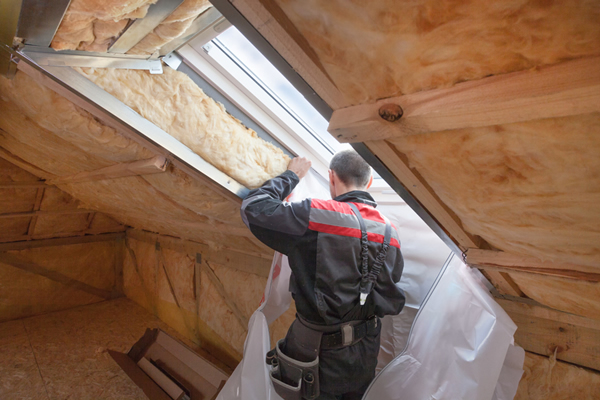 Residential contractor installing skylight on home project.
