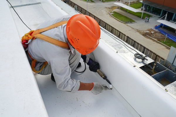 Roofer welding a seam on a PVC roof.