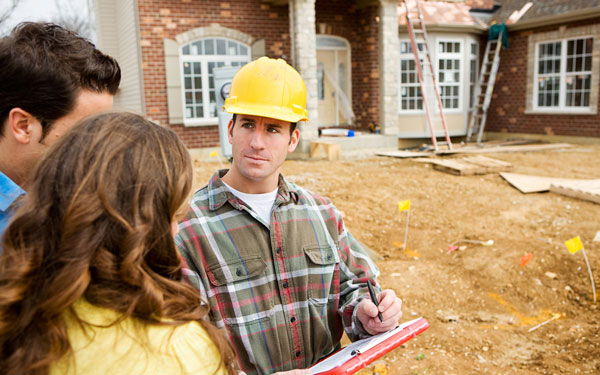 Clients communicating with contractor outside of a brick home