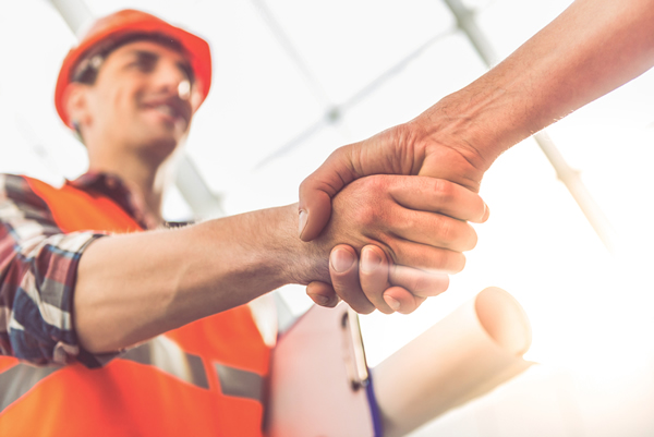 Roofing contractor shaking hands with new lead.