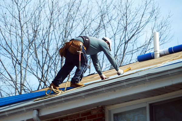 Contractor in hard hat and tool belt repairing a roof