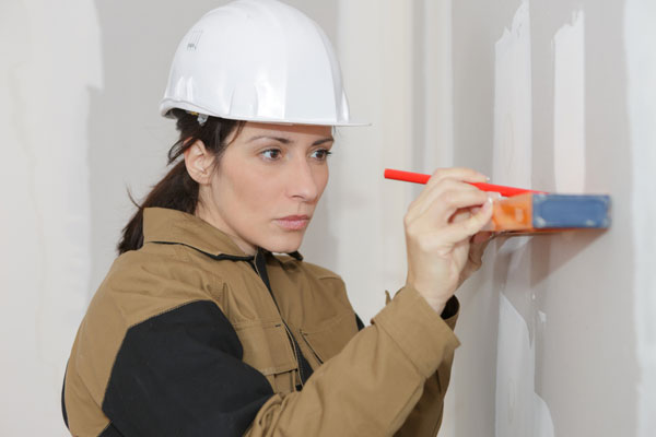Contractor marking drywall with a pencil and level